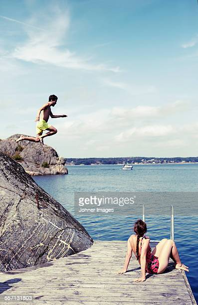 Woman watching man jumping into water