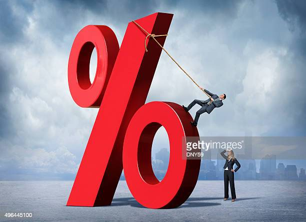 woman watching man scale very large percentage sign - percentage sign stock pictures, royalty-free photos & images