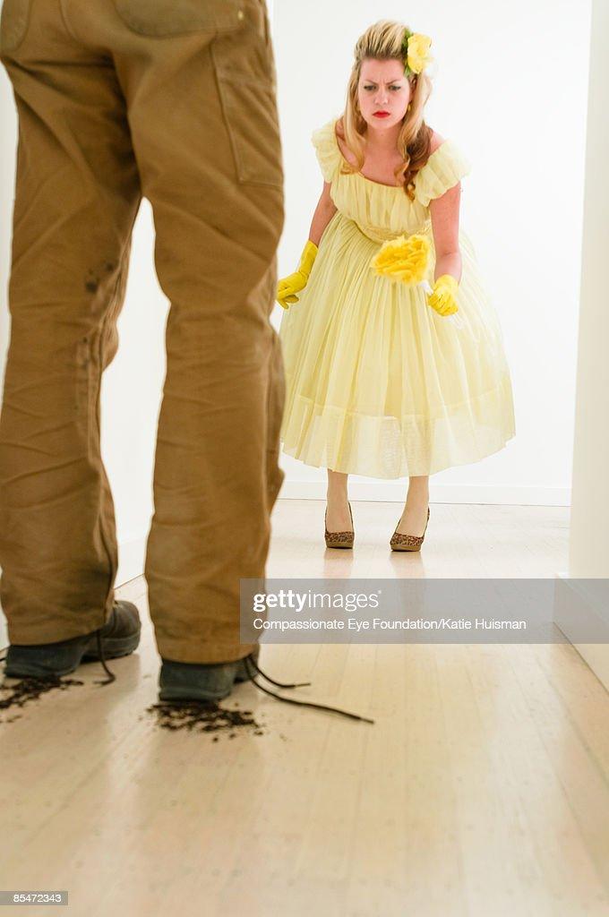 Woman watching man track dirt onto clean floor : ストックフォト