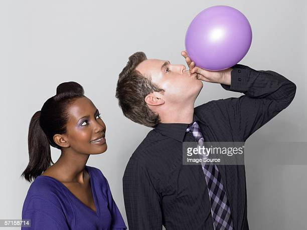 Woman watching man with balloon