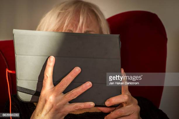 woman watching movie from tablet - obscured face stock pictures, royalty-free photos & images