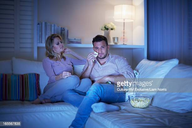 Woman watching movie with sad boyfriend