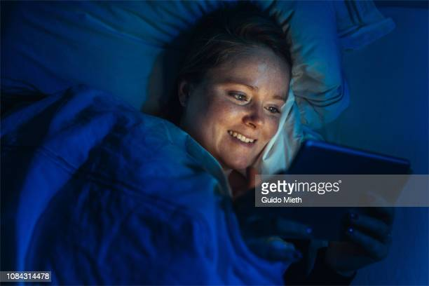 Woman watching movie with tablet pc at night.