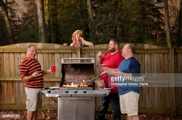 Woman watching neighbors barbecuing food