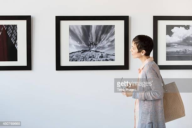 woman watching photographs in art gallery - ausstellung stock-fotos und bilder