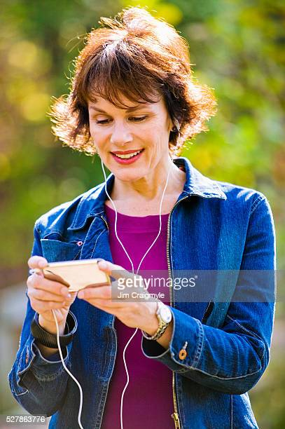 woman watching podcast on mp3 player - jim craigmyle stock pictures, royalty-free photos & images