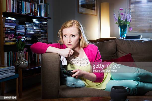 Woman watching sad movie on television.