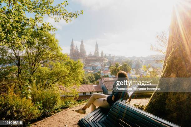 woman watching santiago de compostela cathedral at sunrise, park and sunny sky. galicia, spain - santiago de compostela stock pictures, royalty-free photos & images