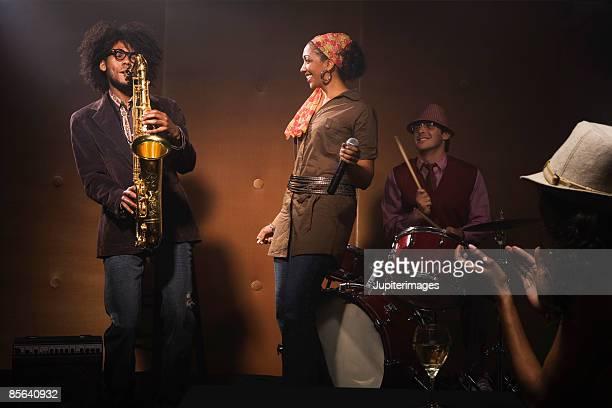Woman watching saxophone player performing jazz in nightclub