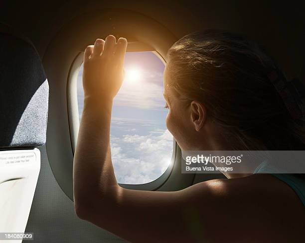 Woman watching sky from airplane's window.