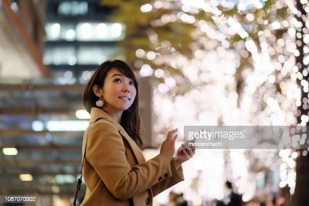 路上照明のスマート フォンを見ている女性 - 丸の内 ストックフォトと画像