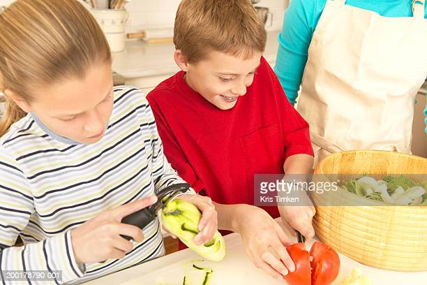 woman watching son and daughter (9-11) cut vegetables for salad - 皮をむく ストックフォトと画像