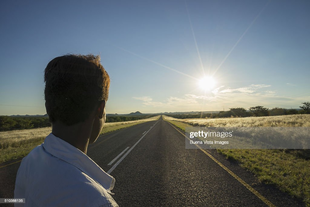 Woman watching sun setting on an empty road : Stock Photo