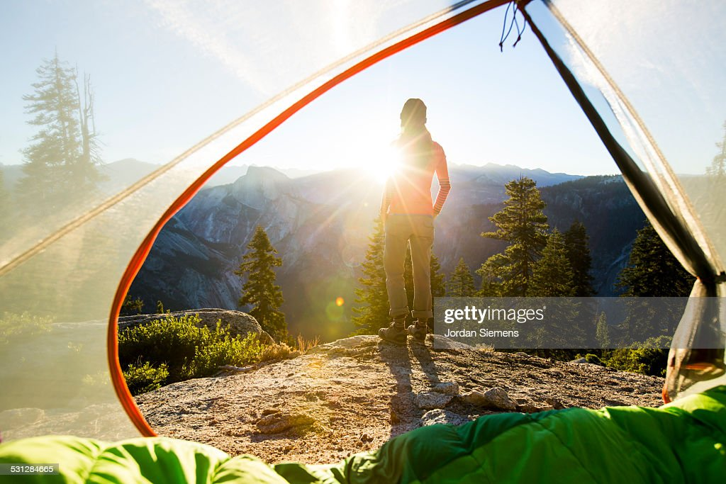 A woman watching sunrise from a tent. : Stock Photo