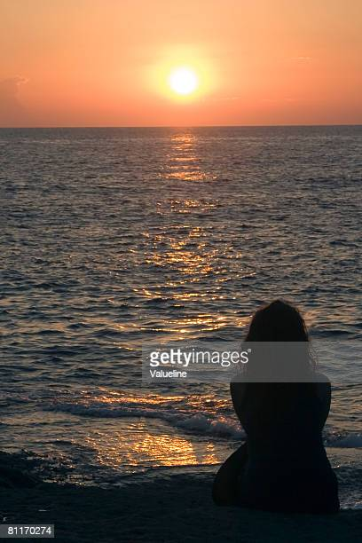 woman watching sunset at the beach - backpage stock photos and pictures