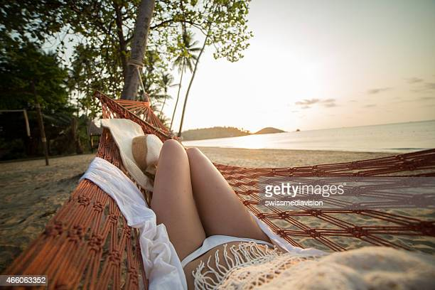 Woman watching sunset from hammock on exotic beach