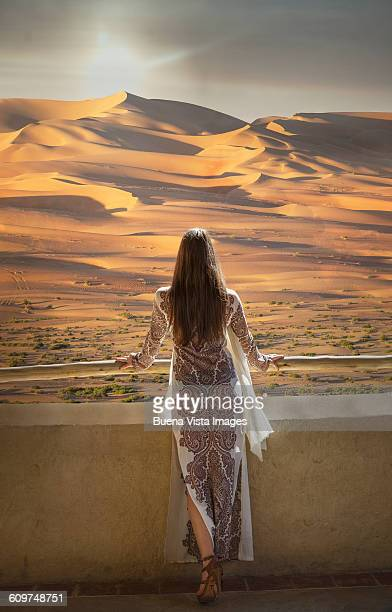 Woman watching sunset in the desert