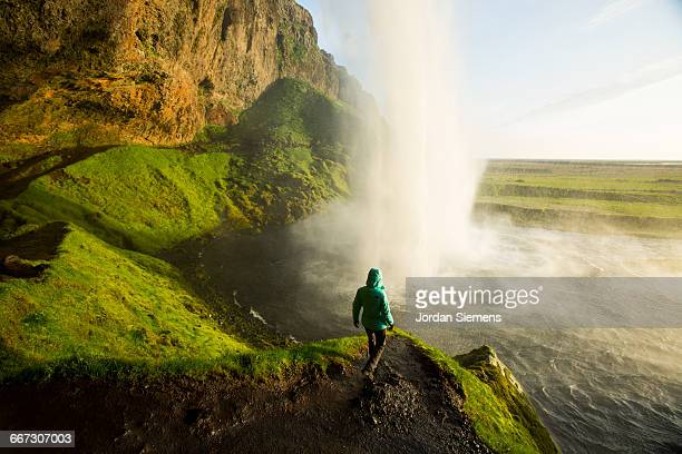 a woman watching sunset near a waterfall. - majestätisch stock-fotos und bilder
