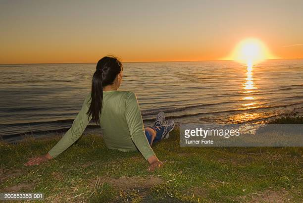 Woman watching sunset over ocean from cliff, rear view