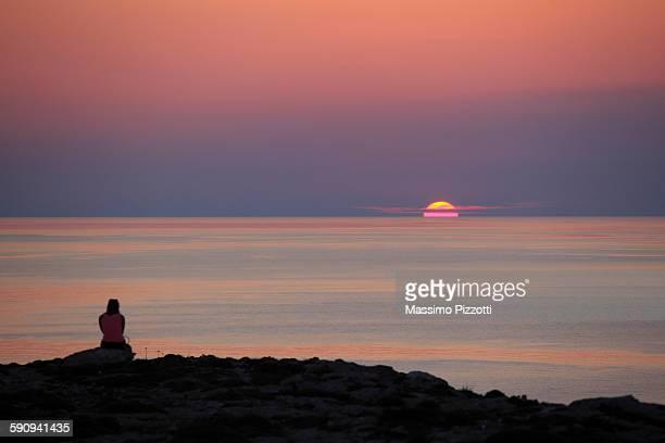 woman watching sunset over the sea - massimo pizzotti foto e immagini stock