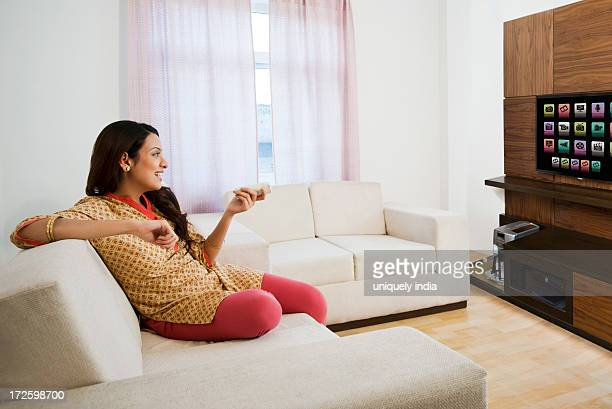 woman watching television in a living room - tv housewife stock photos and pictures