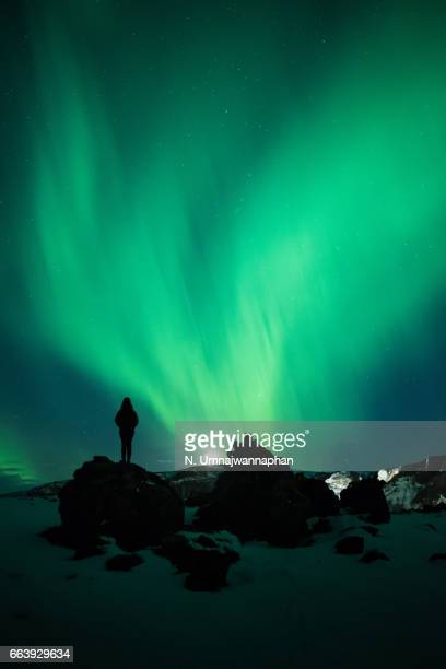 A woman watching the aurora borealis in southern Iceland