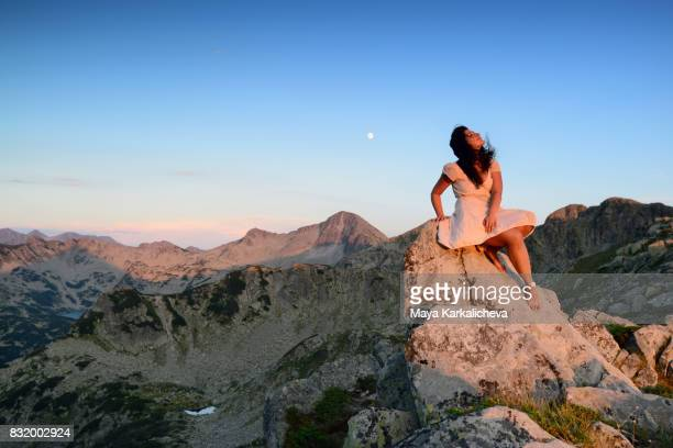 woman watching the sky at sunset below the moon - pirin mountains stock pictures, royalty-free photos & images