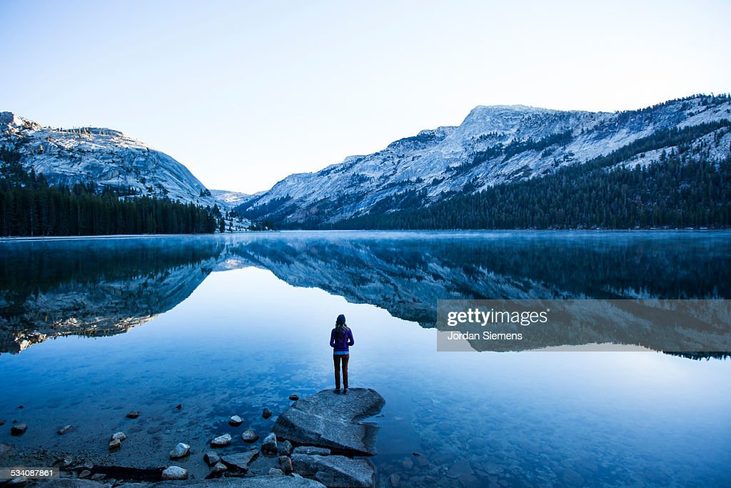 A woman watching the sunrise over a lake. : Stock Photo