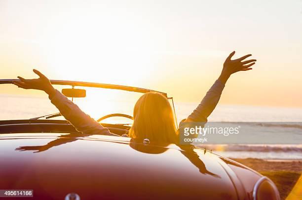 Femme en regardant le coucher de soleil dans une décapotable.