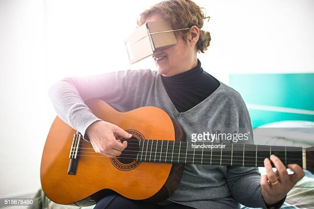 woman watching the virtual reality device simulator with guitar