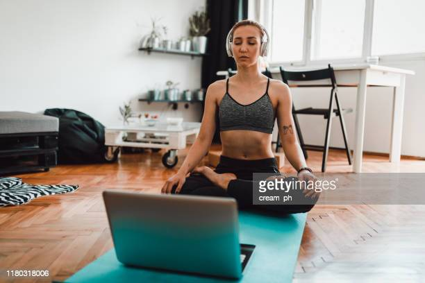 woman watching tutorial on laptop and doing yoga at home - net sports equipment stock pictures, royalty-free photos & images