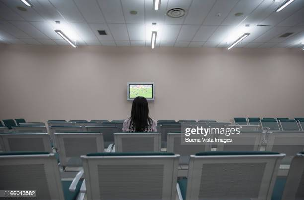 woman watching tv in an empty hall - insight tv stock-fotos und bilder