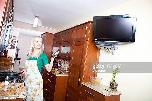 woman watching tv in kitchen while cooking - tv housewife stock photos and pictures