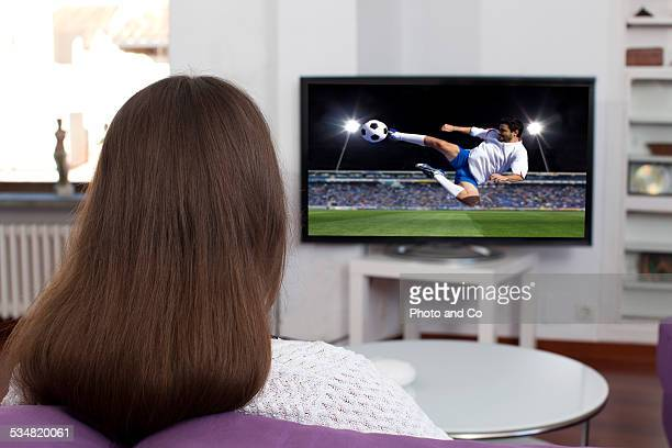 woman watching tv indoors - seulement des jeunes femmes photos et images de collection