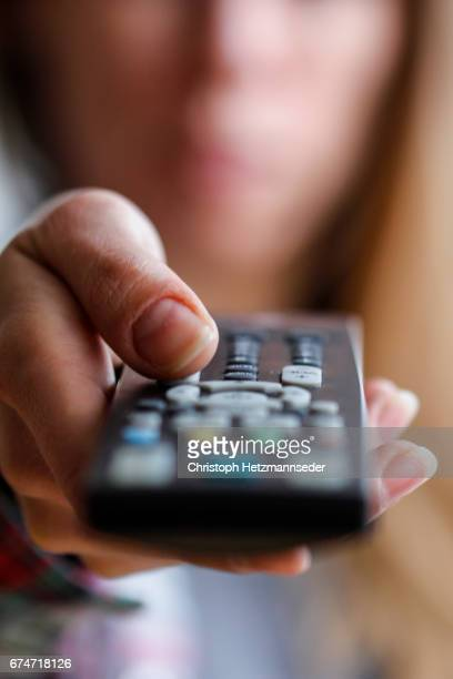 woman watching tv - changing channels stock photos and pictures
