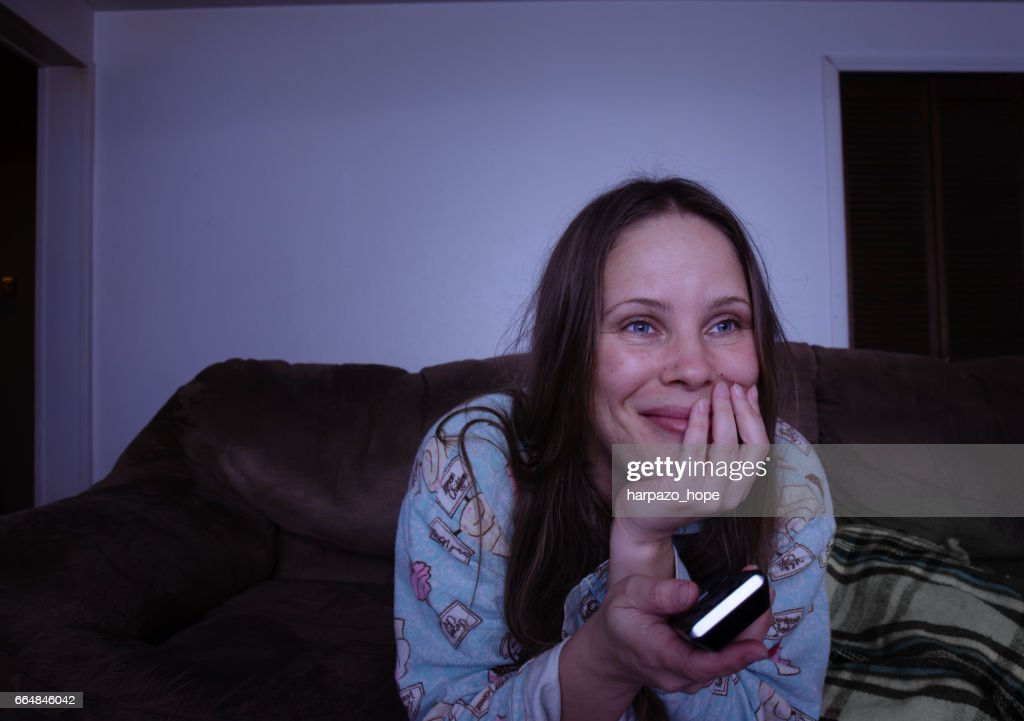 Woman watching TV while holding the remote. : Stock Photo