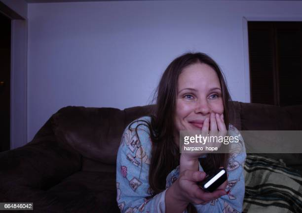 Woman watching TV while holding the remote.