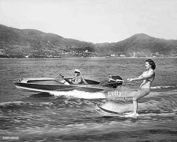 A woman water skis on the bay with another speedboat running along beside her Acapulco Mexico 1955