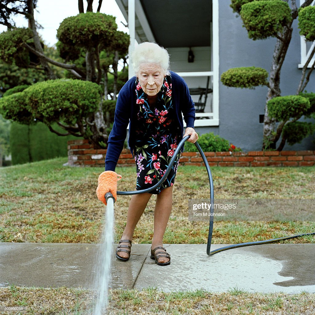 Woman watering her front lawn : Stock Photo