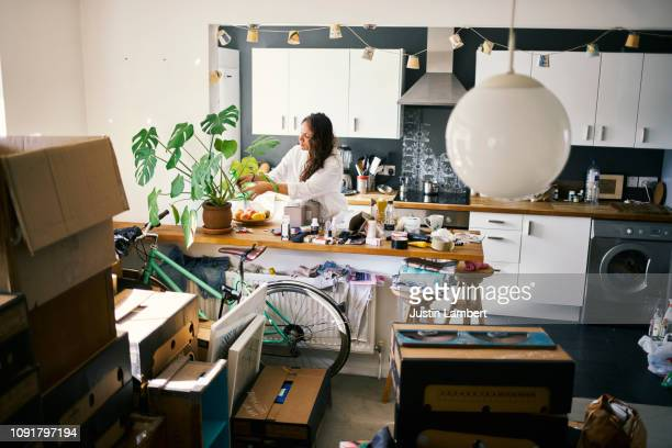 woman watering her plants in the process of moving house - messy stock pictures, royalty-free photos & images