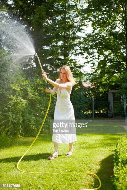 Woman watering lawn, Bavaria, Germany