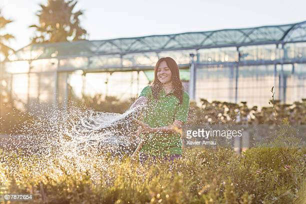 Woman watering plants at garden center