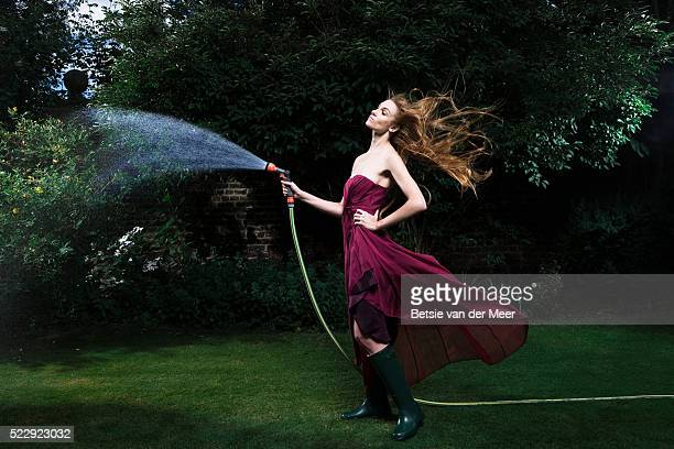woman watering plants in garden - abendkleid stock-fotos und bilder