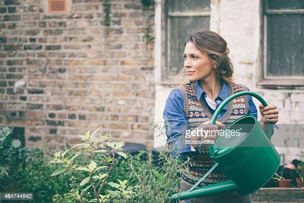 Femme eau les plantes dans le jardin urbain (Londres, Royaume-Uni).