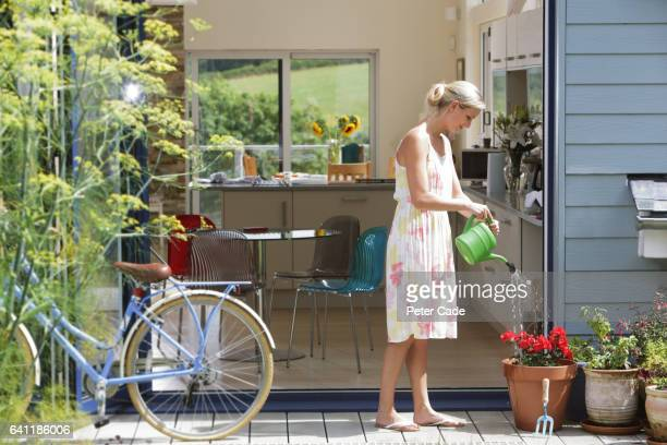 Woman watering plants outside of house