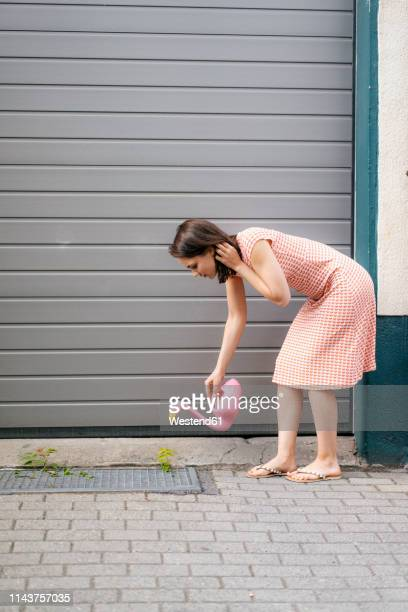 woman watering plants with a flamingo can in an urban street - flamingo heart stock pictures, royalty-free photos & images