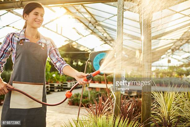Woman watering plants with a hose in a gardencenter.
