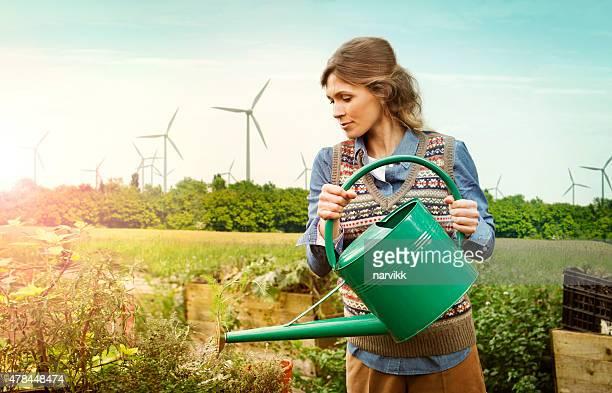 Mulher de abeberamento plantas com vento exploração atrás