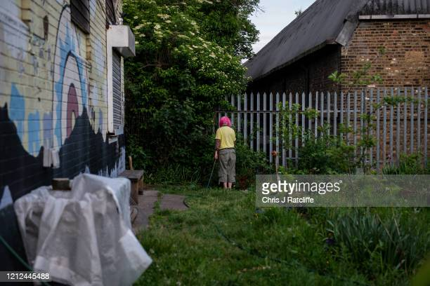 Woman waters her allotment as the sun sets in Finsbury Park on May 9, 2020 in London, England. The UK is continuing with quarantine measures intended...