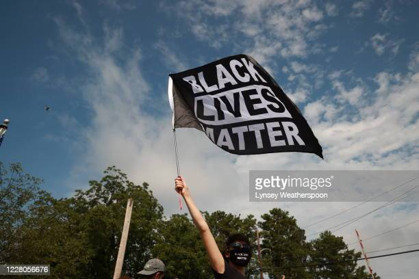 A woman waves a Black Lives Matter flag during a farright rally on August 15 2020 near the downtown of Stone Mountain Georgia Georgia's Stone...